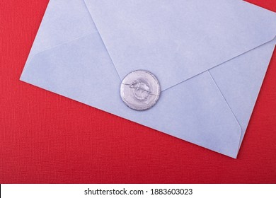 a blue envelope with a wax stamp love on a red background. love letter, background for Valentine's day, mother's day