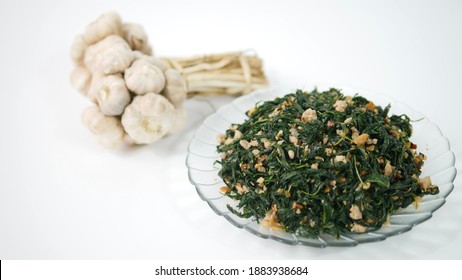 A bunch of fresh garlic and a plate of stir Fried Jute Leaves or Mulukhiyah leaves with ground pork  on white background