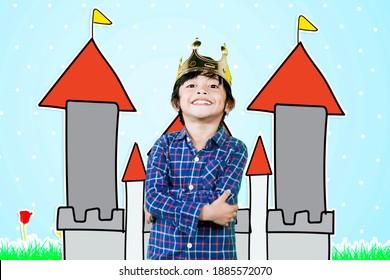 Selbstbewusster kleiner Junge, der eine Krone trägt, während er mit gezeichnetem Schlosshintergrund steht