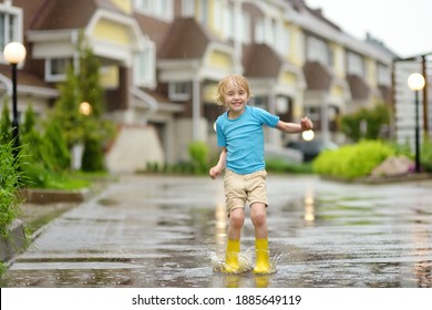 Little boy wearing yellow rubber boots jumping in puddle of water on rainy summer day in small town. Child having fun. Outdoors games for children in rain.