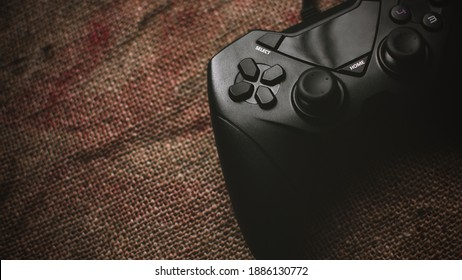 PC game controller placed on a sack cloth with added vignette to create a 16:9 wallpaper for PCs and iMac.