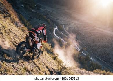 エクストリームライダーがオフロードクロスエンデューロバイクで砂の山頂を登る。背景に美しい山々の風景、日差しの中でカラフルな秋の森と川