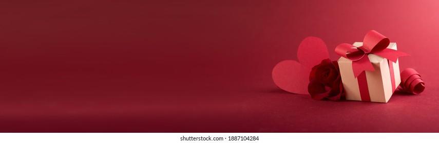 手作りのギフトボックス、紙カットリボン、弓、テキスト用のスペースのある赤い背景にたくさんのハートが付いたペーパーアートバレンタインデーのコンセプトバナー。