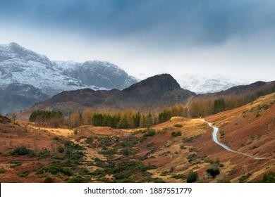 雪をかぶった山々と暗い冬の雲のある田舎を通る一本道。ラングデール、湖水地方、英国。