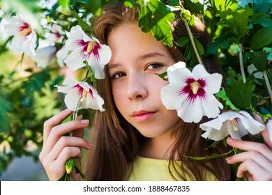 glückliche Kindheit. fröhliches hübsches Kind am blühenden Baum im Freien. Ferienzeit. Sommermode und Schönheit. schönes jugendlich Mädchen mit Hibiskusbuschblume. Kid Spring Fashion Style.