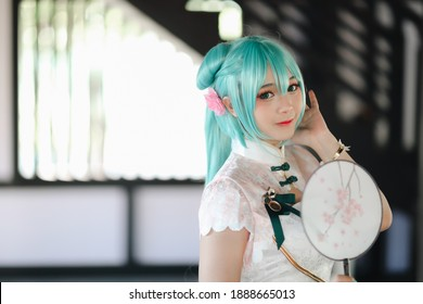 Japan anime cosplay portrait of a girl with chinese dress costume in chinese garden