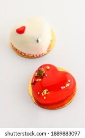 Ein Kuchen in Herzform. Zwei herzförmige Cupcakes auf weißem Hintergrund. Valentinstag. Vertikales Foto