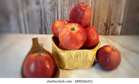 Rote Äpfel in Holzschalen auf einem Marmortisch