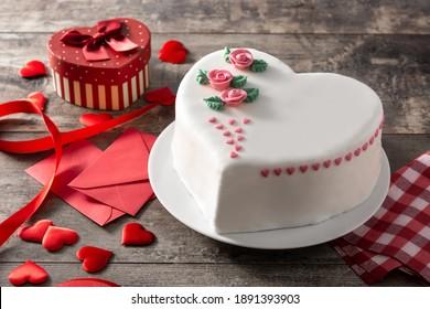 Herzkuchen für Valentinstag, Muttertag oder Geburtstag, verziert mit Rosen und rosa Zuckerherzen auf Holztisch