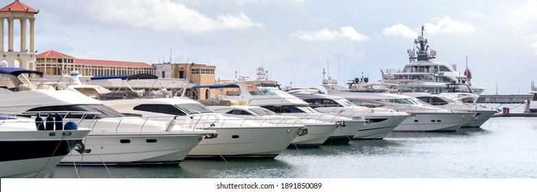 Yachts and speed boats at harbor. Power boats moored in marina. Sea coast pier. High class lifestyle. Yachting. Expensive toys. Sea transport. Journey. Expensive boats at the pier.
