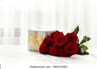 A bouquet of red roses and a gift box on the table in the interior. Love confession. Valentine's day celebration