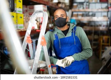 保護マスクの倉庫作業員は、金物店の脚立と工具棚の隣に立っています