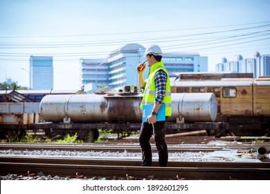 検査中のポートレートエンジニア、建設プロセスの鉄道のチェック、鉄道駅での作業のチェック。作業中の安全ユニフォームと安全ヘルメットを着用しているエンジニア。