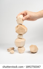 Tumi-ishi puzzle game. A woman or a girl places her hand on another block of wood on top of an unstable tower. The process of the game. Stones for Rock Balance.