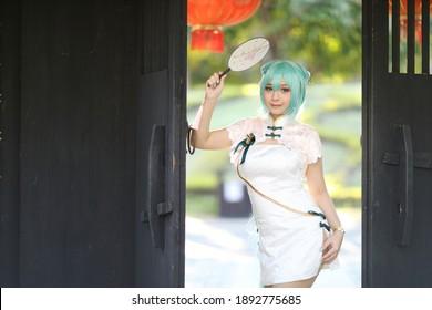 Japanisches Anime-Cosplay-Porträt eines Mädchens mit chinesischem Kostüm im chinesischen Garten