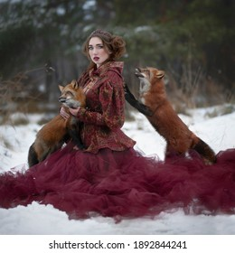 Art photo of a woman in red and two red foxes