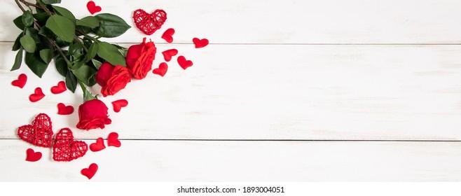 白い背景の上の赤いバラとハートの花束。バレンタインデー、バナー形式。テキストの場所。