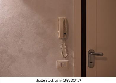 Una pared blanca con un intercomunicador colgado en la pared, un botón de encendido y una puerta blindada (Pesaro, Italia, Europa)