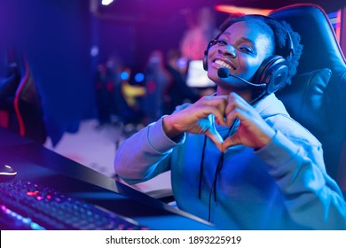 Streamer African beautiful girl shows heart sign with hands professional gamer playing online games computer, neon color.