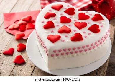 Pastel de corazón para el día de San Valentín, el día de la madre o el cumpleaños, decorado con corazones de azúcar en la mesa de madera