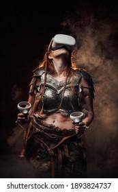 Barbaarse Scandinavische vrouw vechter in lichte pantser met virtual reality headset en joysticks vormt op donkere smokey achtergrond.
