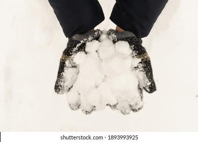 Handschoenen met koude ijzige sneeuwbal, concept winter en leuke sneeuwspellen, sneeuwballengevecht