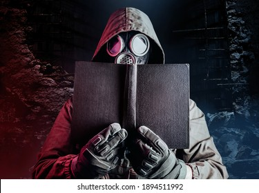Photo of stalker soldier in soviet gas mask holding old book on destructed ruined background.