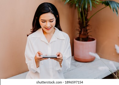 Asian woman playing games on smartphone while sitting on a concrete bench surrounded with pots of green plants with a desert sand colored wall in her background. Gaming addict outdoors