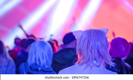 Pink hair teenage girl with anime cat ear partying and cheering at rock concert in front of stage of nightclub - rear view. Bright colorful stage lighting. Nightlife and entertainment concept
