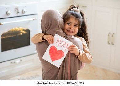Lächelndes kleines Mädchen, das Grußkarte für glücklichen Muttertag mit gezeichnetem rotem Herzen hält und ihre muslimische Mutter umarmt. Liebevolle islamische Familie, die zu Hause zusammenhält, Nahaufnahmeaufnahme mit freiem Raum
