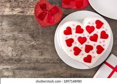 Herzkuchen für Valentinstag, Muttertag oder Geburtstag, verziert mit Zuckerherzen auf Holztisch