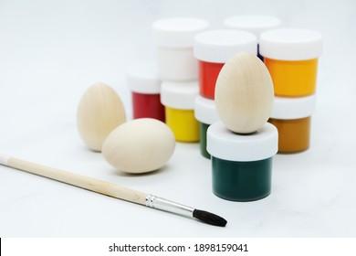 Hölzerne Ostereier, bunte Farben und Pinsel zum Dekorieren von Souvenirs zur Osterfeier. Künstlerische Arbeit, handgemacht, Kreativität mit Kindern zur Dekoration an Ostern.
