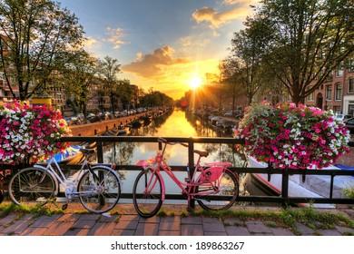 Schöner Sonnenaufgang über Amsterdam, Niederlande, mit Blumen und Fahrrädern auf der Brücke im Frühjahr