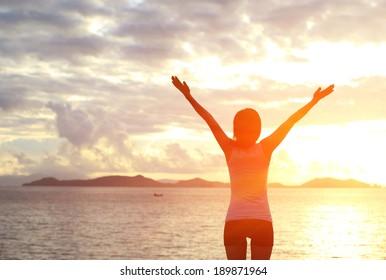 海で日の出に腕を広げて応援する女性