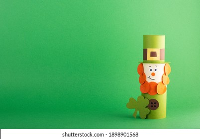 Green cute Leprechaun made of handmade paper on a green background, space for text. Cultural and religious holiday St. Patrick's Day