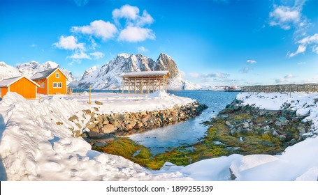 Erstaunliche Winteransicht des Sakrisoy-Dorfes und der schneebedeckten Berge auf Hintergrund. Beliebtes Touristenziel auf den Lofoten. Ort: Sakrisoy, Moskenesoya, Lofoten; Norwegen, Europa