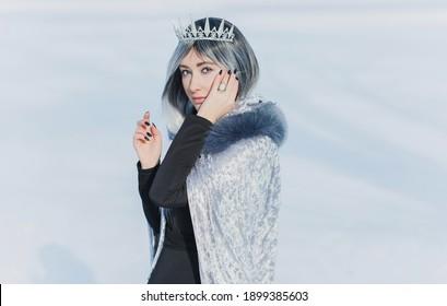 北極圏のおとぎ話のシーン、冷たいファンタジールックの女性、銀の髪、マント、雪の日のドレス。コスプレコンセプト