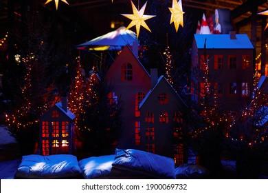 Festival y Feria de Año Nuevo. Casas de madera de colores decoradas y estrellas navideñas. Fondo borroso y foco seleccionado. Copie el espacio para insertar texto.
