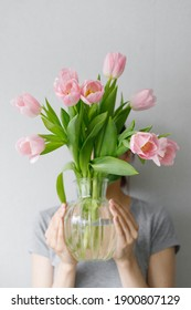 girl holding pink tulips in a glass vase against a gray wall, florist, bouquet of tulips, pink tulips, gift, flowers as a gift, March 8, Valentine's day, birthday wife, date, flowers for a woman