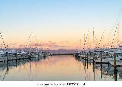 Los barcos y los muelles de Tauranga Marina se reflejan en aguas tranquilas al amanecer.