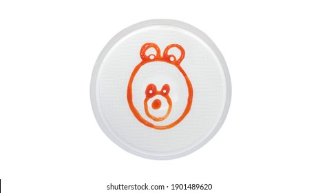 Teddy bear is drawn with ketchup on a plate, teddy bear in a plate is isolated on a white background, cute bear is drawn with sauce.