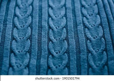 Blauer gestrickter Hintergrund. Wollstoff mit Zopfmuster. Aran-Muster im Zusammenhang mit Stricknadeln.