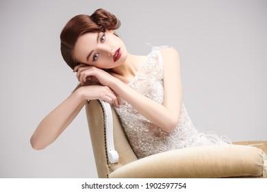 ヴィンテージのアームチェアで豪華な白いドレスを着てポーズをとる美しいシックな女性の肖像画。20代のイブニングメイクとヘアスタイル。