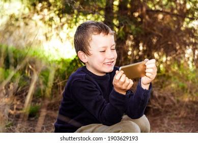 Een jongen met een uitdrukking van groot vermaak geniet van het bekijken van video's op zijn smartphone terwijl hij in een bos is.
