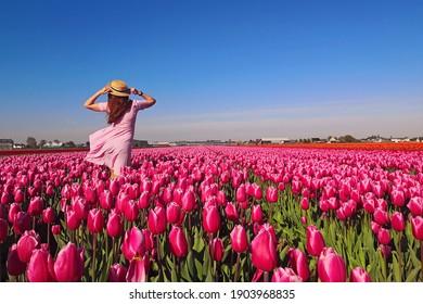 Turista de la mujer joven en vestido rosado y sombrero de paja que se coloca en campo floreciente del tulipán. Tiempo de primavera