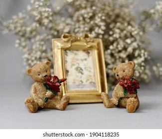 Idea de regalo del día de San Valentín. Marco de fotos dorado y figuritas de ositos de peluche con ramos rojos. Lindo concepto actual.