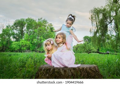 Little cute girls with butterfly wings on a large tree stump among the tall green grass. Selective focus. Blurred background.
