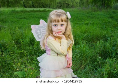 Little cute girl with butterfly wings on a large tree stump among the tall green grass. Selective focus. Blurred background.