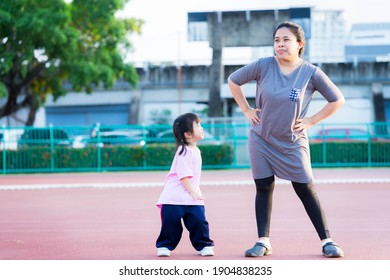 Mother and daughter are exercising. Cute girl laughed happily and looked at her mom. The mother made a irksome face be merciful for the little child. The family enjoyed the evening sport activities.