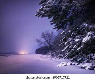 Un hermoso campo nevado con ventisqueros, el borde del bosque y una ciudad con linternas en la distancia. Una vista fuera de la ciudad con colores inusuales en el cielo y en la nieve después del atardecer.